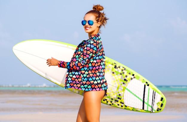 Retrato de verão ao ar livre de uma mulher sorridente correndo com uma prancha de surfista perto do oceano azul