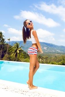 Retrato de verão brilhante de garota sexy hipster se divertindo na festa na piscina, segurando seus rabos de cavalo e flertando, alegria, férias, ilha tropical.
