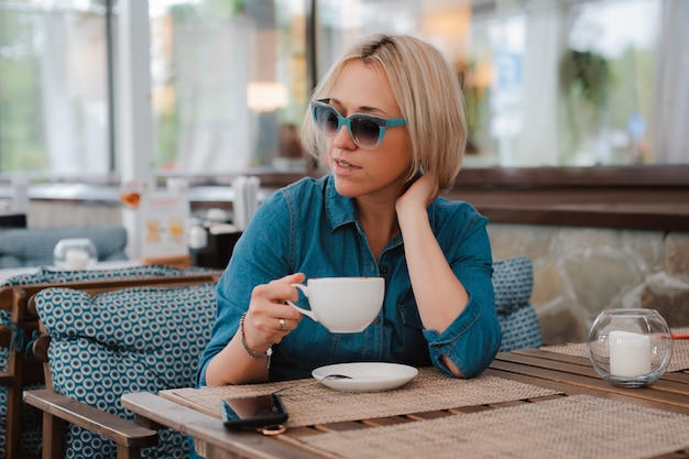Retrato de verão close-up de uma jovem em elegantes óculos de sol com uma xícara de café da manhã, vestido elegante azul brilhante.
