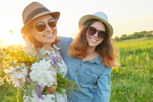 Retrato de verão da feliz mãe e filha na natureza