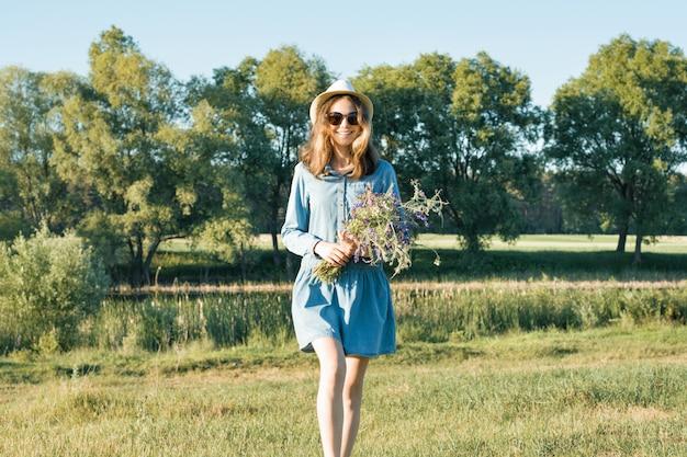 Retrato de verão da menina adolescente com buquê de flores silvestres
