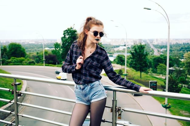 Retrato de verão da menina bonita magro hipster em uma camisa xadrez e shorts jeans em elegantes óculos escuros e batom azul