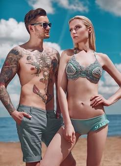 Retrato de verão da moda lindo casal recebendo um bronzeado