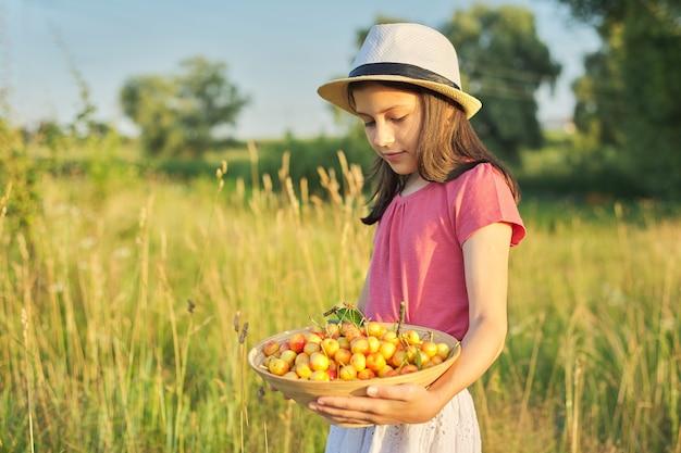 Retrato de verão de menina em um prado com tigela de cereja doce amarela, criança feliz no verão com colheita de baga na natureza