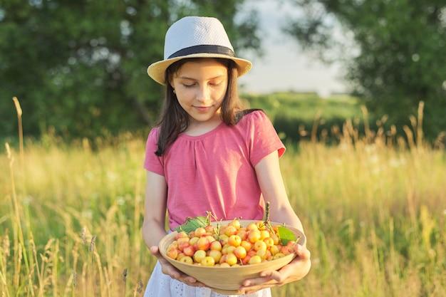 Retrato de verão de menina em um prado com tigela de cereja doce amarela, criança feliz no verão com colheita de frutas vermelhas na natureza