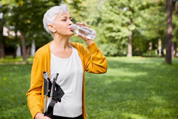 Retrato de verão de uma cansada mulher branca de cabelos grisalhos na casa dos sessenta anos bebendo água de uma garrafa de plástico, se refrescando após a atividade física e posando ao ar livre com bengalas