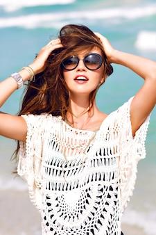 Retrato de verão de uma jovem elegante, céu azul, oceano límpido, aproveite as férias em um país tropical, alegria, estilo de férias