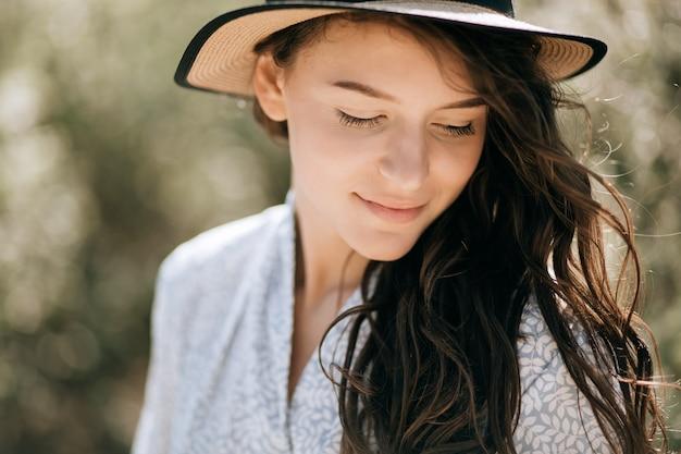 Retrato de verão de uma jovem mulher feliz no chapéu