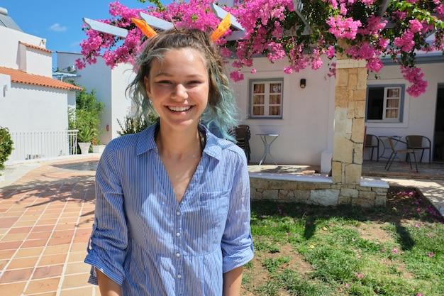 Retrato de verão de uma linda adolescente, sorridente, mulher de cabelo azul, espaço ao ar livre, casa branca, prédio com flores cor de rosa, cópia espaço