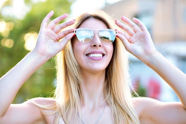 Retrato de verão ensolarado primavera de mulher loira feliz desfrutar de lindo dia quente, sorrindo e fechando os olhos, usando óculos elegantes da moda, humor positivo.