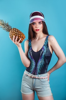 Retrato de verão moda mulher bonita no visor de sol rosa e abacaxi sobre parede azul