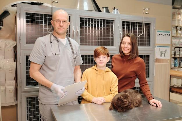 Retrato de veterinário profissional e família com gato sorrindo para a câmera em pé na clínica veterinária