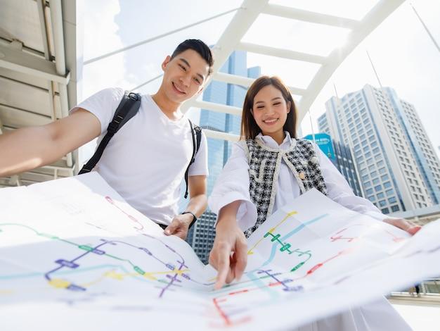 Retrato de visão de ângulo amplo de um jovem amante sorridente e feliz, um viajante asiático em pé olhando o mapa do metrô em papel junto com uma mulher apontando o mapa para encontrar a estação alvo com o primeiro plano do mapa desfocado
