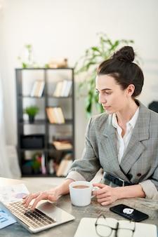 Retrato de vista lateral da empresária bem-sucedida usando laptop enquanto trabalhava no escritório e tomando café