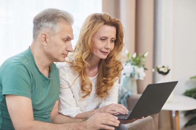 Retrato de vista lateral de casal maduro moderno usando laptop juntos enquanto está sentado no sofá no interior da casa