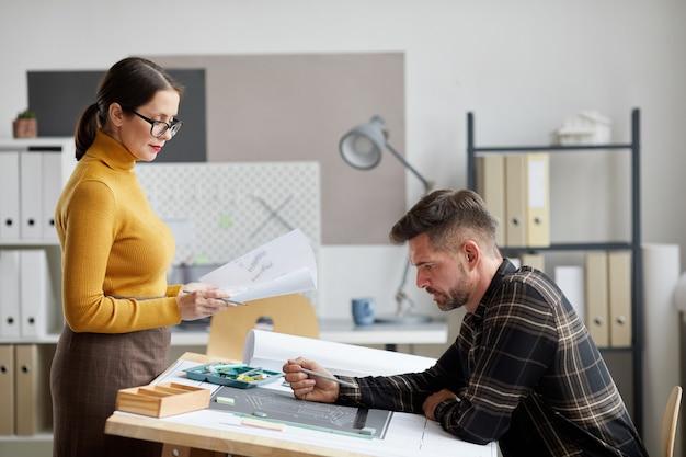 Retrato de vista lateral de dois arquitetos adultos discutindo plantas enquanto trabalham juntos no escritório
