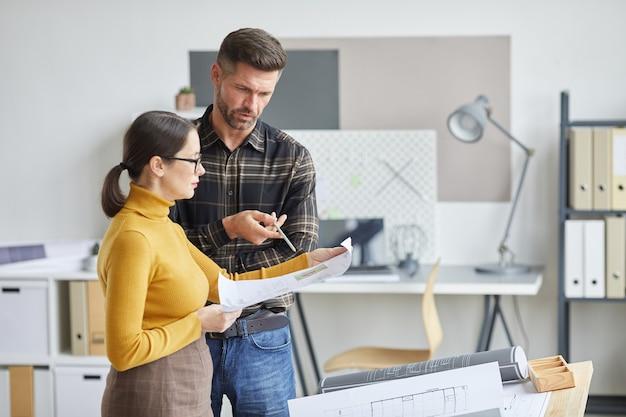 Retrato de vista lateral de dois arquitetos discutindo plantas enquanto trabalhavam juntos no escritório,