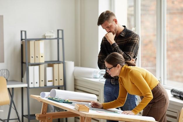 Retrato de vista lateral de dois arquitetos olhando para a planta baixa enquanto trabalhava em plantas no local de trabalho,