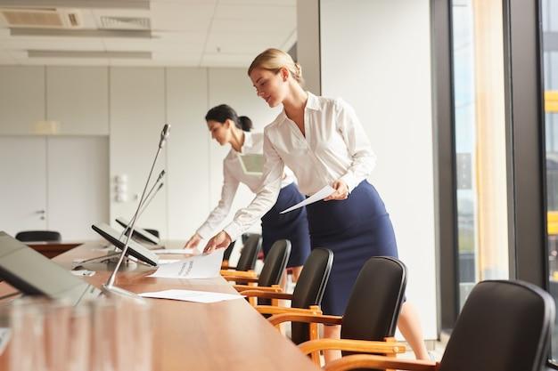 Retrato de vista lateral de duas secretárias exibindo documentos enquanto prepara a sala de conferências para um evento de negócios.
