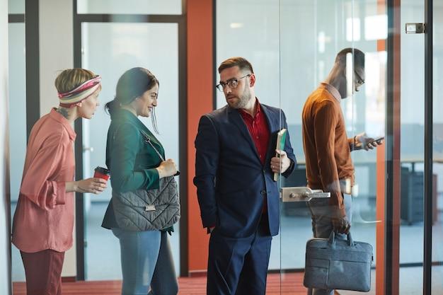 Retrato de vista lateral de executivos em pé na fila do escritório, foco no empresário barbudo maduro falando com uma jovem mulher, copie o espaço