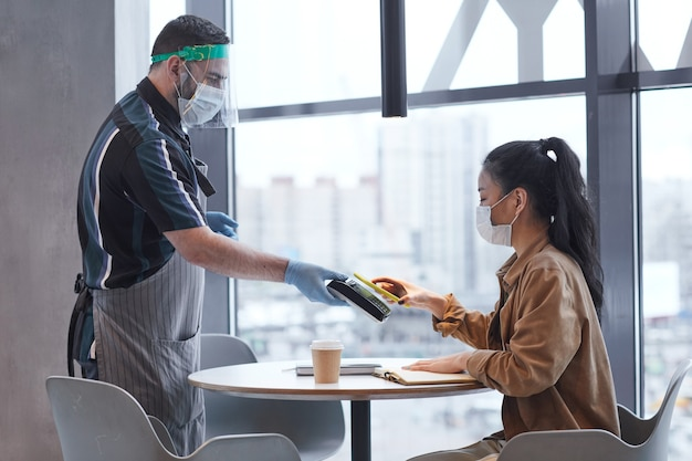 Retrato de vista lateral de garçom usando protetor facial e luvas enquanto atendia uma cliente em um café com medidas de segurança ambiciosas