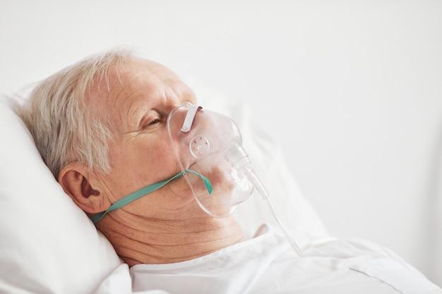 Retrato de vista lateral de homem idoso doente, deitado em uma cama de hospital com máscara de suplementação de oxigênio, copie o espaço