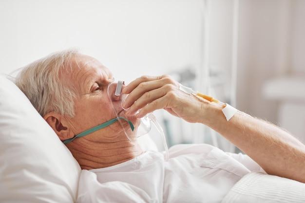 Retrato de vista lateral de homem idoso doente deitado em uma cama de hospital com máscara de suplementação de oxigênio e iv, copie o espaço