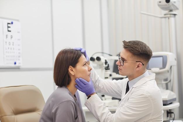 Retrato de vista lateral de jovem oftalmologista abrindo o olho de uma paciente