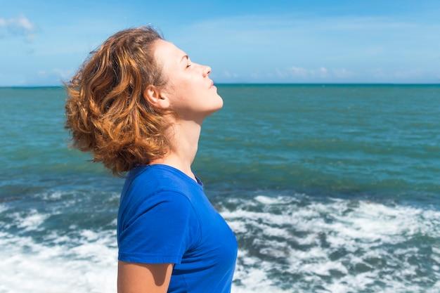 Retrato de vista lateral de mulher relaxada, respirando profundamente o ar fresco no mar