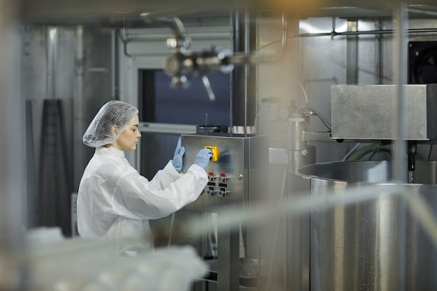 Retrato de vista lateral de operária operando unidades de máquinas em uma fábrica de produção de alimentos limpos, copie o espaço