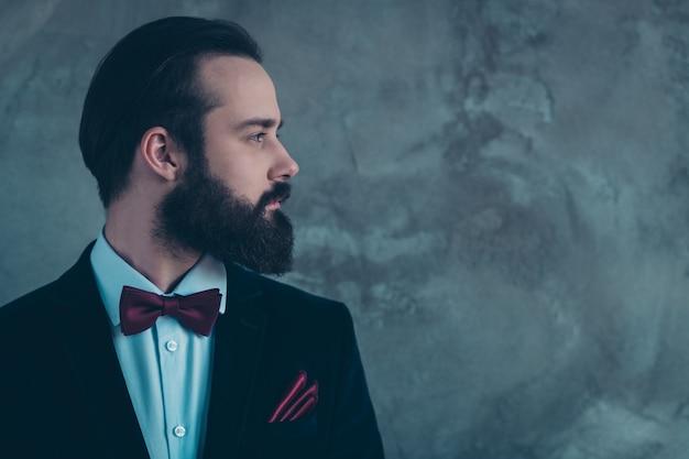 Retrato de vista lateral de perfil de close-up de seu cara atraente barbudo sério focado vestindo smoking isolado sobre parede industrial de concreto cinza