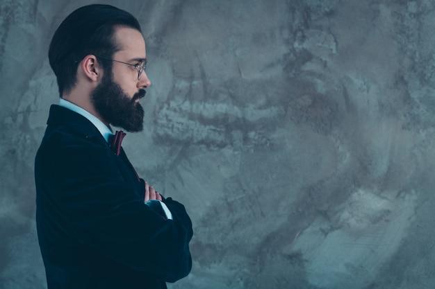 Retrato de vista lateral de perfil de close-up de seu ele agradável representante sério barbudo usando smoking de veludo braços cruzados cópia espaço isolado sobre parede industrial de concreto cinza