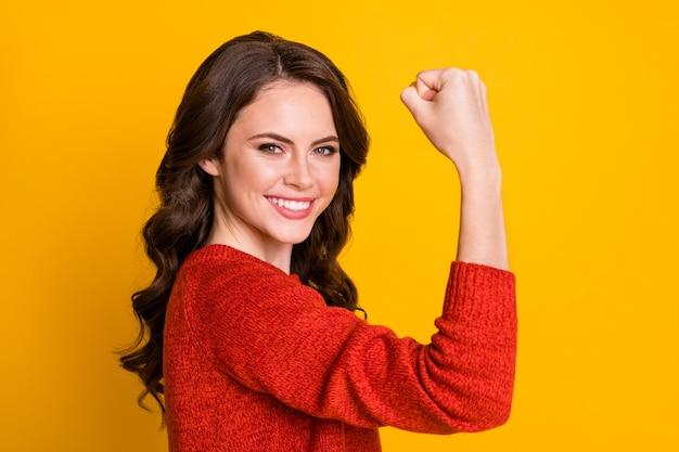 Retrato de vista lateral de perfil de close-up dela ela bonita atraente conteúdo adorável alegre alegre menina de cabelos ondulados mostrando braço forte isolado em fundo de cor amarela vibrante de brilho vívido brilhante