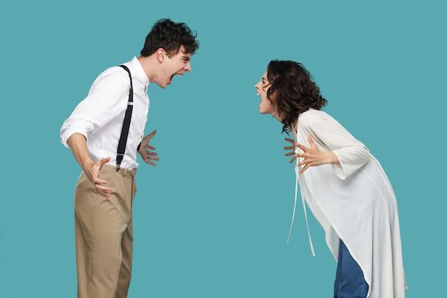 Retrato de vista lateral de perfil de dois agressivos parceiros morenos em pé e gritando um com o outro. conflito entre amigos, parceiros ou família. estúdio interno tiro isolado sobre fundo azul.