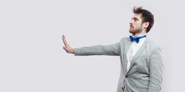 Retrato de vista lateral de perfil de homem barbudo bonito sério em terno cinza casual, gravata azul em pé e olhando em linha reta com sinal de gesto de mão parada. tiro do estúdio, isolado no fundo cinza claro.