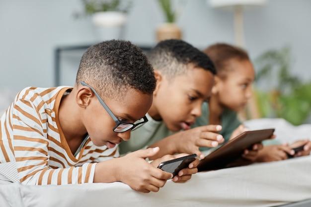Retrato de vista lateral de três crianças em fila usando gadgets enquanto está deitado na cama em casa copie o espaço