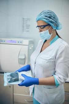 Retrato de vista lateral de um assistente médico sério segurando o equipamento pronto para usar no trabalho