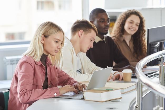 Retrato de vista lateral de um grupo de alunos usando laptops enquanto estudava na faculdade, loira digitando em primeiro plano,