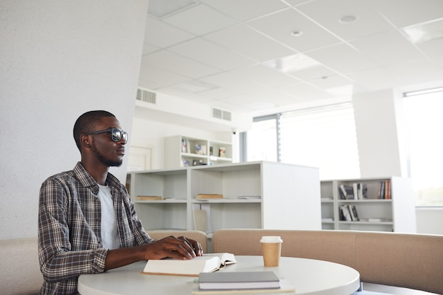 Retrato de vista lateral de um homem afro-americano cego lendo livro em braille na biblioteca,