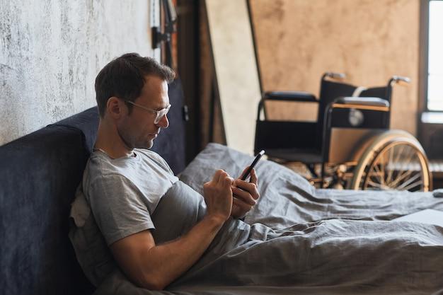Retrato de vista lateral de um homem moderno com deficiência usando smartphone na cama, cadeira de rodas no fundo, espaço de cópia