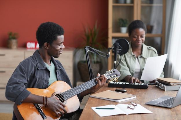 Retrato de vista lateral de um jovem afro-americano tocando violão enquanto compõe música em um estúdio de gravação caseiro, copie o espaço