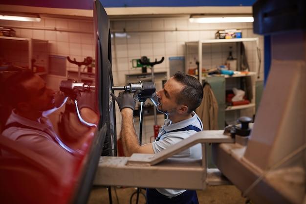 Retrato de vista lateral de um mecânico de automóveis maduro trocando as rodas de um carro de luxo vermelho em uma oficina mecânica, copie o espaço