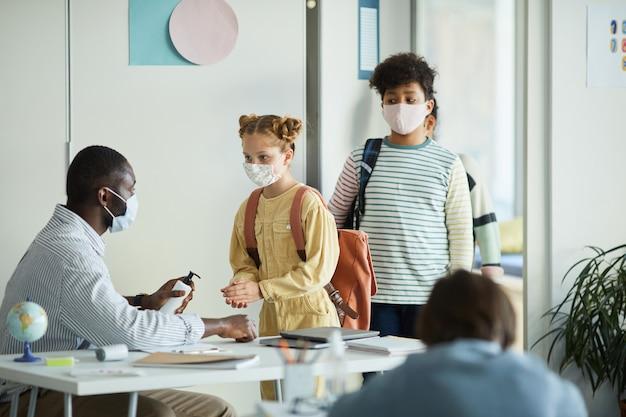 Retrato de vista lateral de um professor ajudando crianças a higienizar as mãos ao entrar na sala de aula na escola, medidas de segurança ambiciosas