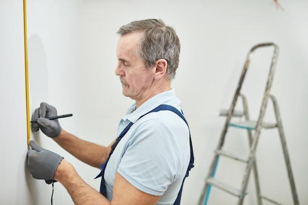 Retrato de vista lateral de um trabalhador da construção civil maduro medindo a parede enquanto reforma a casa, copie o espaço