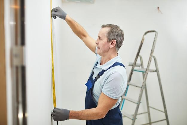 Retrato de vista lateral de um trabalhador da construção civil sênior medindo a parede durante a reforma da casa, copie o espaço