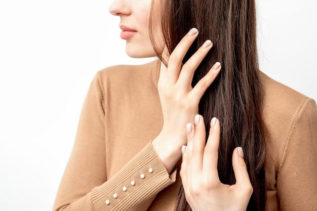 Retrato de vista lateral de uma bela jovem morena caucasiana tocando seu cabelo com dedos bem cuidados em branco