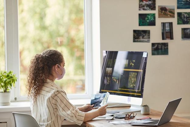 Retrato de vista lateral de uma jovem fotógrafa usando máscara enquanto usa o computador na mesa em casa com software de edição de fotos na tela, copie o espaço