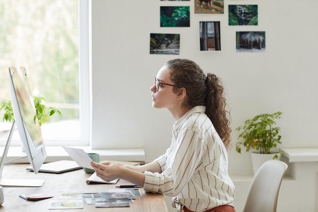 Retrato de vista lateral de uma jovem moderna segurando fotos enquanto trabalha no pc no escritório branco, copie o espaço