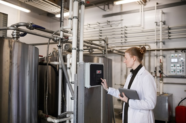 Retrato de vista lateral de uma jovem trabalhadora operando máquinas em uma fábrica de laticínios, copie o espaço