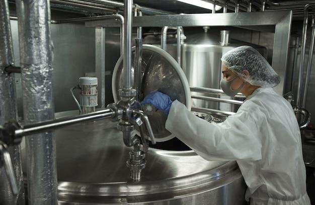 Retrato de vista lateral de uma jovem trabalhadora operando uma máquina de mistura na fábrica de produção de alimentos limpos, copie o espaço